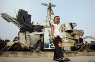 Child stands before remains of US aircraft, including part of a B-52 shot down over Vietnam