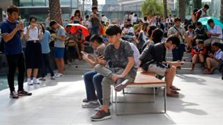 A large group of young Thai people using their phones to play Pokemon Go in Bangkok on 8 August 2016