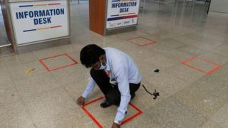 A worker marks a square on the ground to mark social distancing