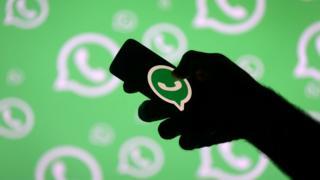 Mão segurando celular com símbolo do WhatsApp