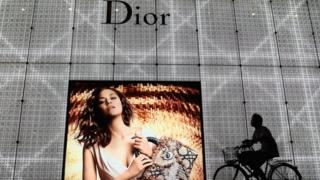 A Chinese man rides bicycle past an advertisement for the Christian Dior store on June 8, 2012 in Beijing, China