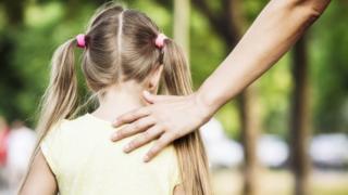 Adult's hand on child's shoulder