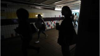 People walking in complete darkness at Clapham Junction station in London