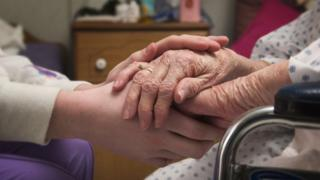 A carer holding an elderly person's hands