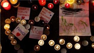 Burning candles, messages and a drawing pay tribute to victims of the truck attack along the Promenade des Anglais on Bastille Day that killed scores and injured as many in Nice, France, 17 July 2016.