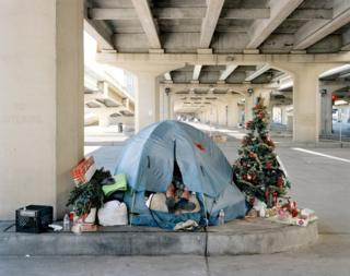 Homeless man in a tent with a Christmas tree