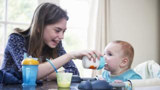 Girl feeding a baby