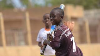 Young Senegalese children playing baseball,