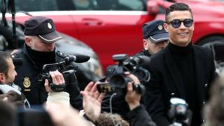 A smiling Ronaldo appears outside court, with TV cameras visible all around him