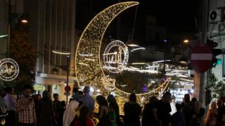 Shoppers in Amman, Jordan walk past a giant Crescent Moon and other light decorations