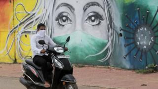 Un joven con mascarilla pasa en motocicleta frente a una valla que ilustra la necesidad de usar mascarillas en Bhubaneswar, India, agosto 10, 2020.