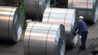 A worker inspects rolls of steel at a factory