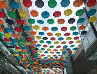 Colourful umbrella's hanging between buildings