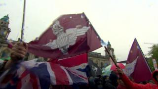 A Union flag and the flag of the parachute regiment are flown at the rally at Belfast City Hall