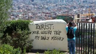 """Barselonada """"Turist. Sizin lüks səyahətiniz, bizim gündəlik əziyyətimizdir"""" yazısı."""