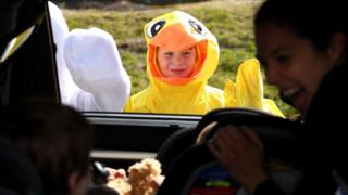 Boston Phillips, 11, dressed as a chick, waves to children during a drive-through Easter photo session at StoryHeights Church on April 11, 2020 in Newton, Massachusetts.