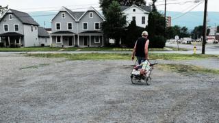 Homem puxando carrinho de compras