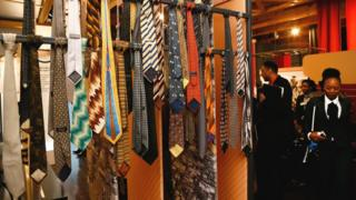 A woman walks past a collection of ties that belonged to South Africa's former President Nelson Mandela, Johannesburg, South Africa - Thursday 28 July 2018