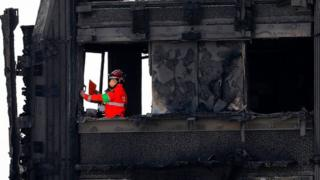 The emergency services work on the charred remains of Grenfell Tower