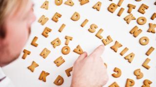 Hombre con galletas de letras