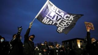 Protesters wave a Black Lives Matter flag outside the Brooklyn Center Police Department. 14 April 2021