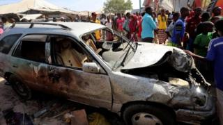 Civilians stand near a car destroyed in an explosion at the Madina district of Somalia (19 February 2017)