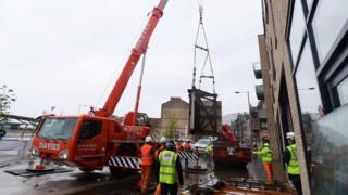 The Banksy being moved into the gallery by a crane