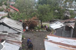 Watu wamesimama karibu na nyumba zilizoharibiwa na miti ilioanguka baada ya kimbunga Kenneth kupiga Comoros