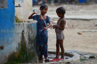 Indian children take a bath at a roadside tap during a hot summer afternoon in Allahabad on June 2, 2019