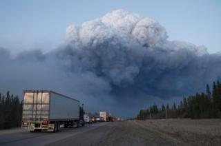 Drivers wait for clearance to take firefighting supplies into Fort McMurray, Alberta