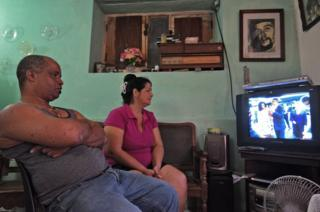 A family in Havana, watch TV coverage of the arrival of US President Barack Obama to Cuba