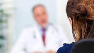 Mulher diante de médico