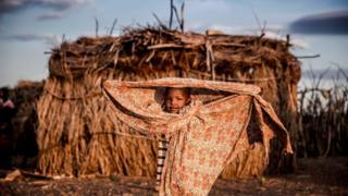 A child belonging to the Turkana community stands next to the family house, covered with a blanket, in the early morning hours in an arid dry area in Morungole, Turkana County, Kenya, on October 3, 2019
