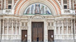 Woman prays in front of a closed Westminster Cathedral on Sunday