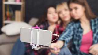 Imagem desfocada de três mulheres jovens fazendo selfie
