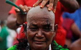 A supporter of Tamil Nadu Chief Minister Jayalalitha Jayaraman gets her head shaved near Jayalalitha's burial site in Chennai, India, December 7, 2016.