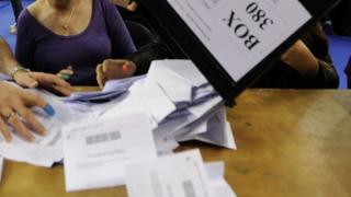 Ballot papers being tipped onto a desk
