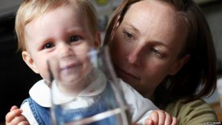 A mum gives her toddler filtered water