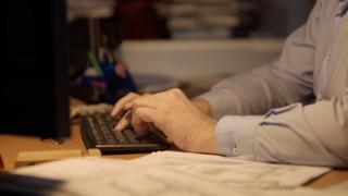 Man types at keyboard at night