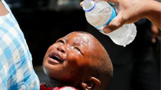 A woman pours water over a child affected by teargas after clashes between police and street vendors in central Harare, Zimbabwe,