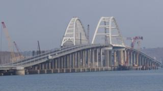 This photo shows the Kerch bridge, with some cranes along its edges, in daylight