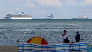 People on the beach at Studland look out at the cruise ships