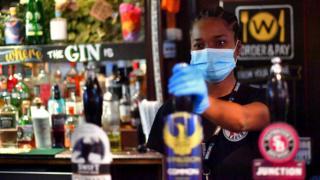 A woman behind a bar in a pub