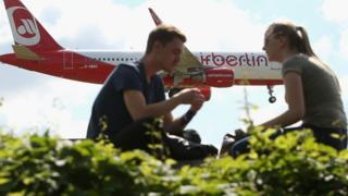 A couple watch as an Air Berlin plane lands at Tegel Airport
