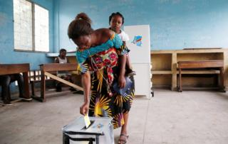 Woman casting her vote with a baby on her back.