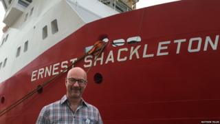 Peter Gibbs in front of the RRS Ernest Shackleton. The ship is red in colour and the name is in big white letters.