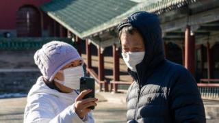 Two people in face masks look at a mobile phone