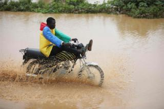 A man wearing a colourful rain-proof jacket is seen riding a motorcycle through brown floodwater. He is balancing his legs close to the handlebars to avoid getting them wet.