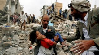 A man carries a girl rescued from the site of a suspected Saudi-led air strike that killed eight members of her family in Sanaa, Yemen (25 August 2017)