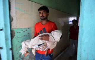 Indian man holds the body of a child